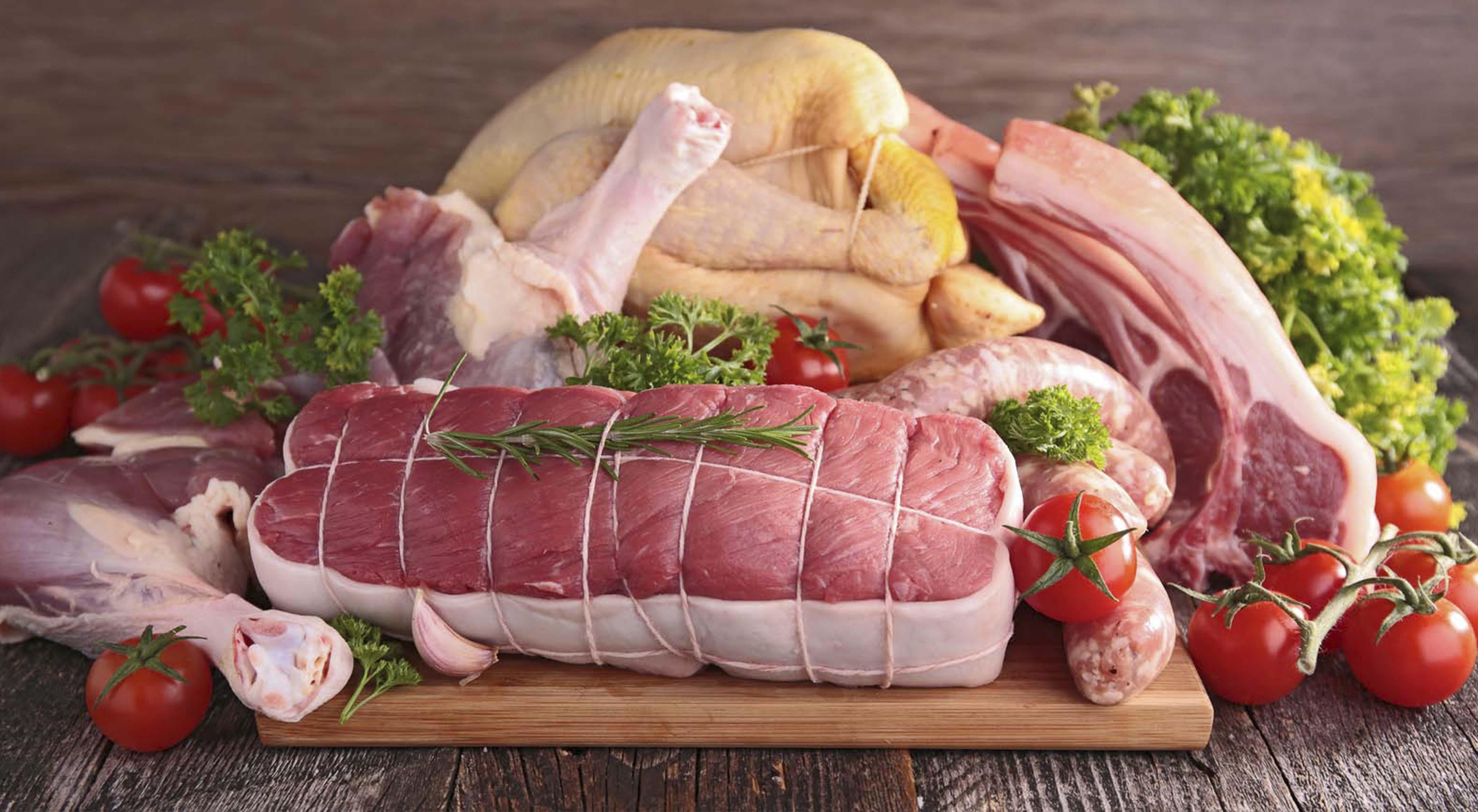 tagliere in legno con carne rossa di pollo pomodori e insalata
