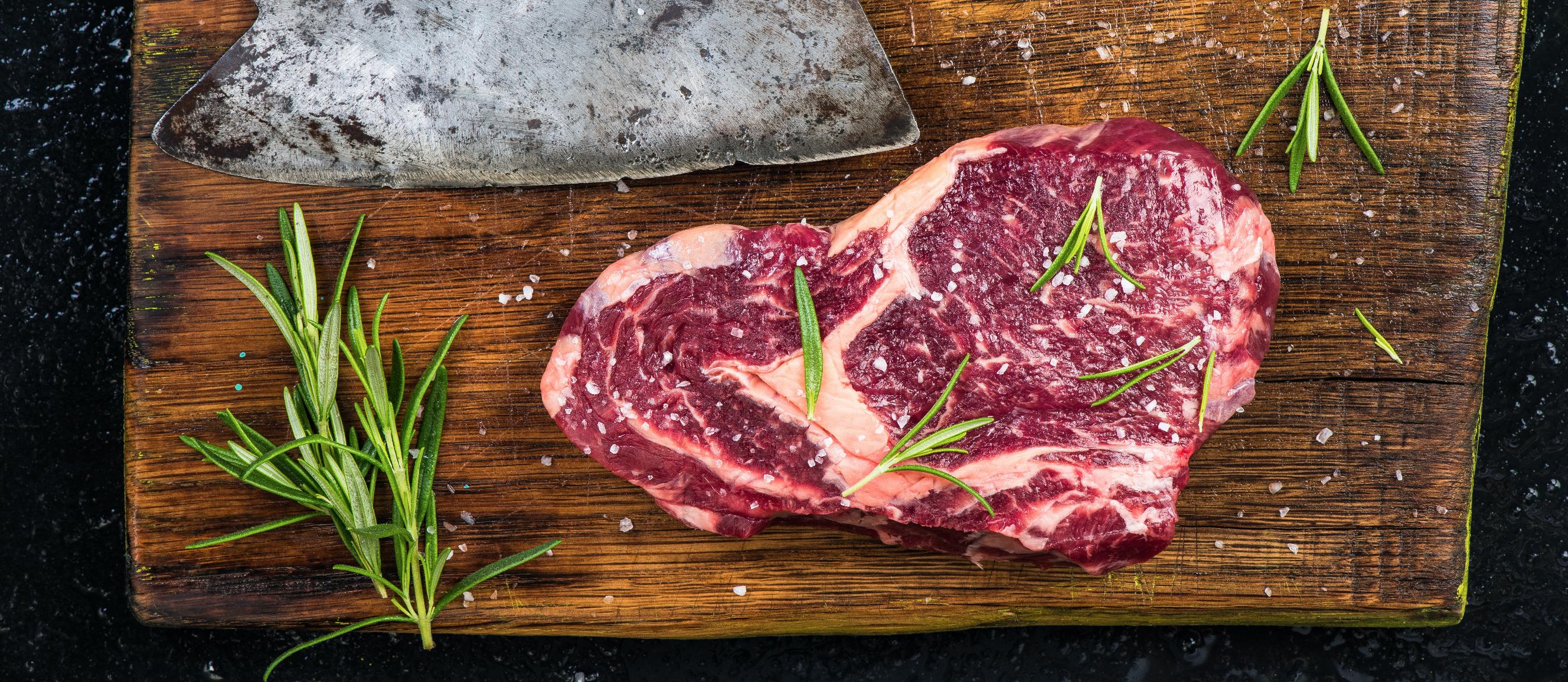 carne grassa con coltello su tagliere in legno